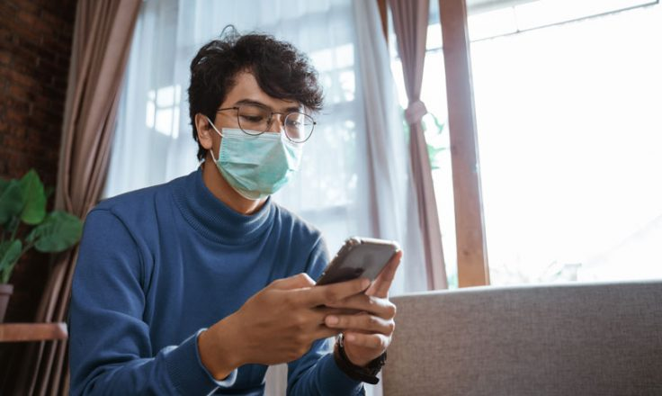 person wearing mask using phone