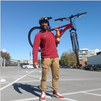 william wearing read shirt and helmet holding a bike