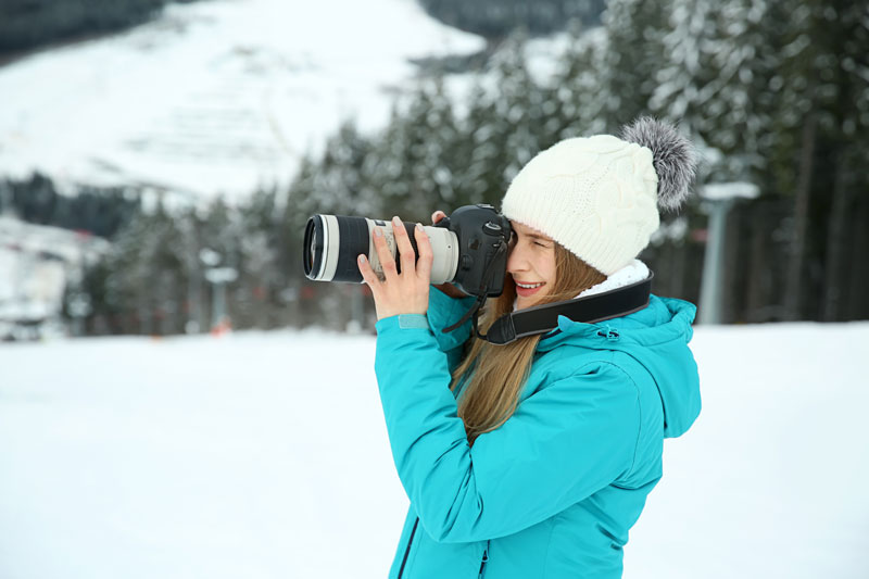 woman using a camera in the snow to film a winter scene