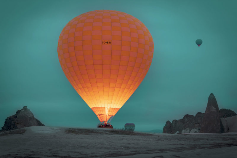 orange hot air balloon lit up at dusk in the mountains