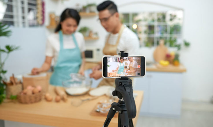 two people recording a cooking video