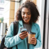 woman smiling at phone holding coffee