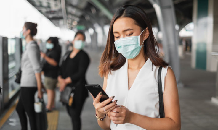 woman wearing mask using phone at train station