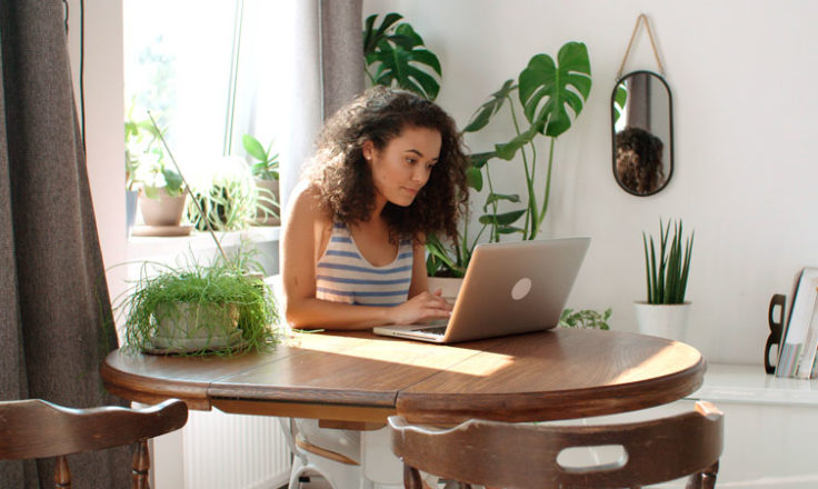 woman using computer surrounded by plants