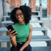 woman sitting on stairs looking at phone
