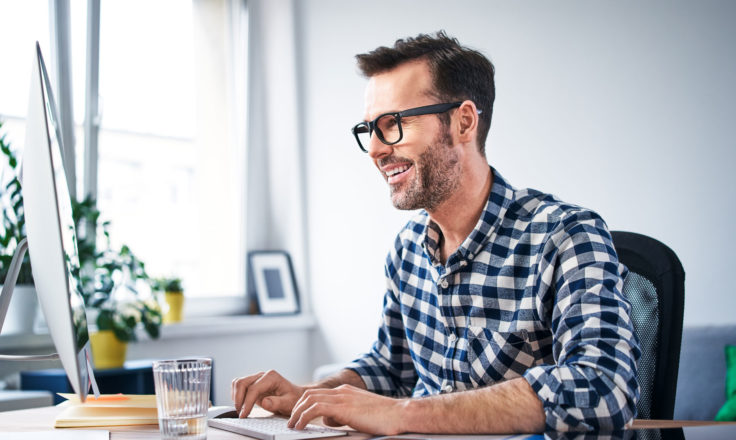 man in a blue and white plaid shirt using a desktop computer at a desk