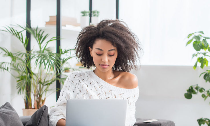 woman looking at her laptop sitting on the couch