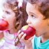 children biting into apples