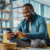 man sitting on couch, looking at phone and smiling