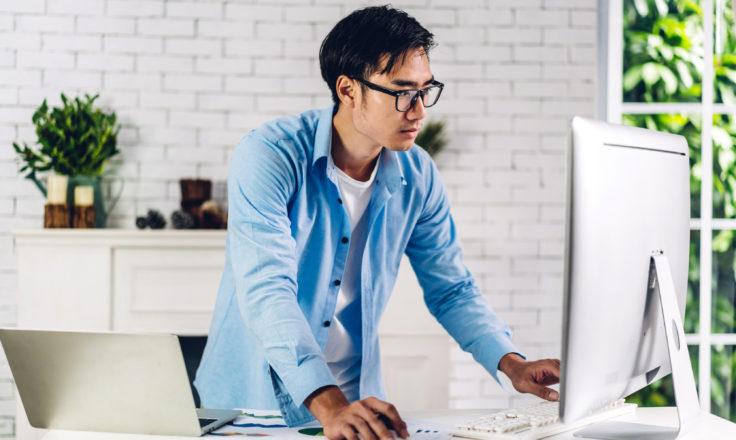 man standing up using a desktop computer